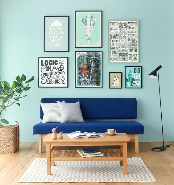 Scandinavian style living room for Spring deep blue couch light wood coffee table modern area rug in light tone natural fiber woven pot for greenery light blue walls well ordered frames of pictures