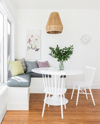 breakfast nook idea L shaped bench seat with gray comforter colorful throw pillows round top dining table in white white dining chairs green centerpiece with glass vase
