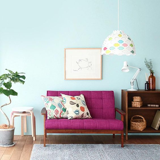 bright purple loveseat with throw pillows bright area rug light blue walls potted houseplant wooden hall console beautiful pendant with colored stain lampshade