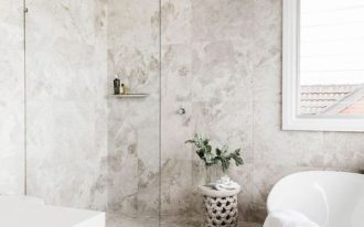 coastal bathroom marble walls and floors modern bathtub in white whitewashed stool with greenery walk in shower with clear glass panel
