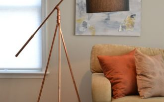 copper tripod floor lamp with black lampshade earthy brown couch with deep orange throw pillows wood floors shag area rug in beige