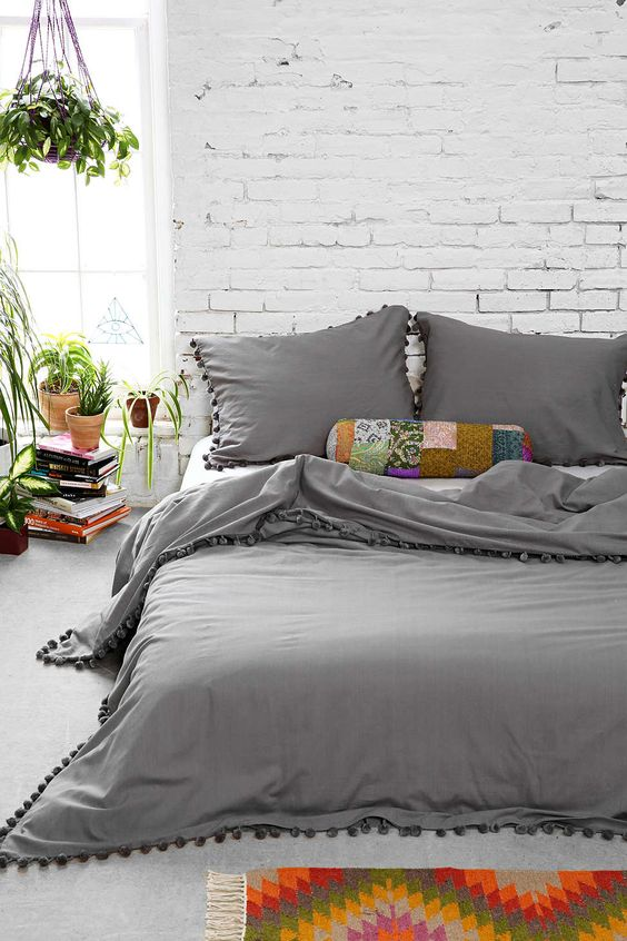 dark gray duvet with ornate balls on edges dark gray pillows with ornate balls on edges white painted brick walls vividly colorful bed mat some potted greenery
