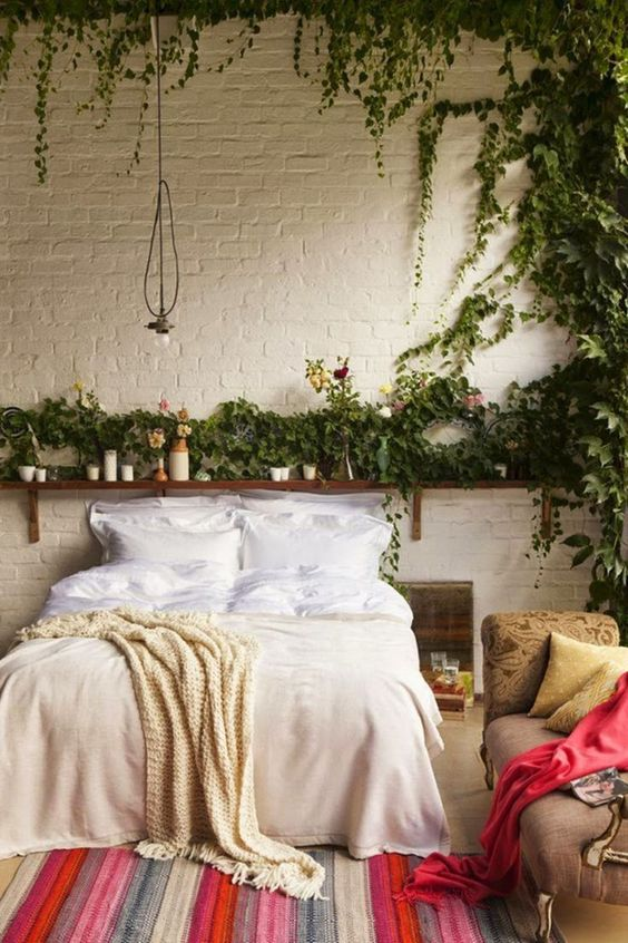 heavy jungle like bedroom decor idea with growing vines white painted brick walls wooden single shelf striped & colorful area rug hand knitted throw blanket