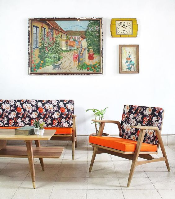 midcentury modern chairs with dark flowery upholstery and orange seat base wooden coffee table in midcentury modern style some wall arts