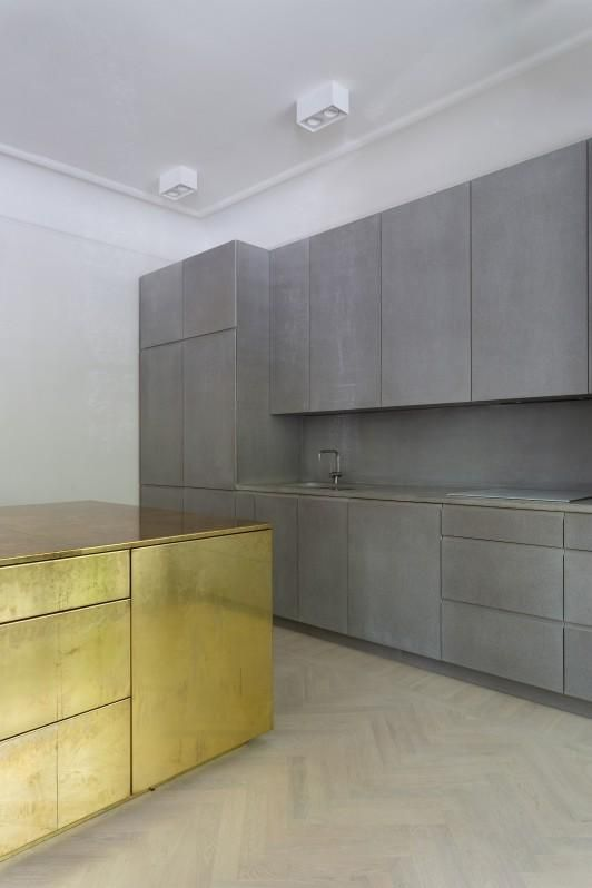 minimalist Brutalism kitchen idea with gold tone accent