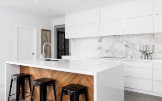minimalist kitchen idea white kitchen island black bar stools flat door cabinetry in white concrete floors marble backsplash