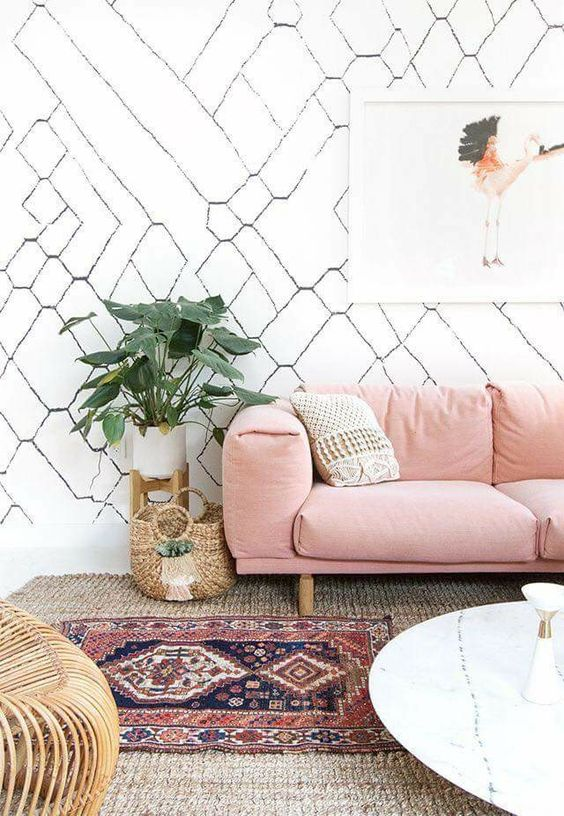 modern bohemian living room idea soft pink couch textured throw pillow double layered rugs modern white wallpaper with line accents round marble top coffee table
