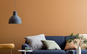 modern living room design bright orange wall paint gray couch white orange throw pillows gray pendant