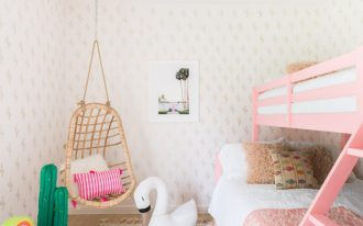 modern maximalist bedroom design wall with ligh wallpaper light fury rug with modern pattern pink painted bed rattan hanging chair modern pendant