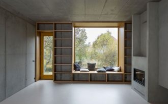 modern minimalist space with wood belvederes some throw pillows integrated wood bookshelves and bench modern fireplace