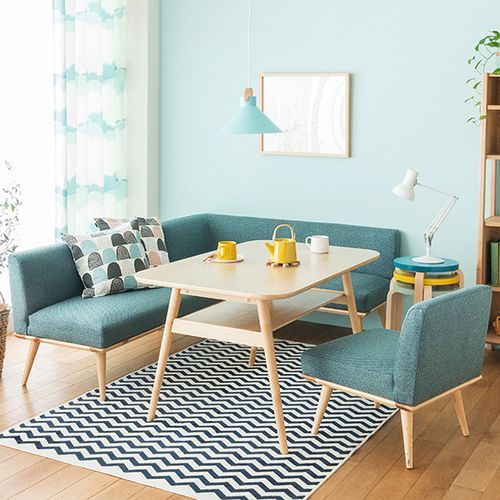 simple & minimalist living room idea L shaped sofa in blue multicolored throw pillows higher wood top coffee table white black area rug light wood floors light blue wall colorful round top side table