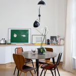 Small Dining Space In Minimalist Style Round Top Dining Table In Dark Tone Simple Dining Chairs In Dark Wood Tone Light Wood Floors White Wall Painting