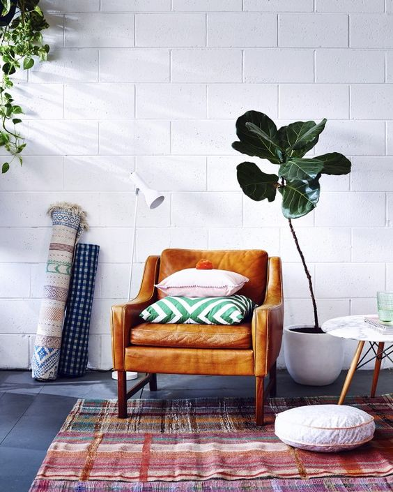 small seating area leather chair with throw pillows shabby & patterned area rug white potted greenery white round shape floor pillow rolled rug with patterns white tiles wall