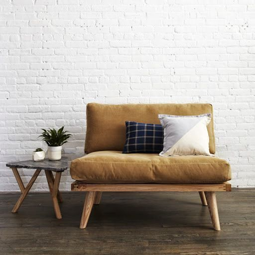 supercalm and supecozy living room white painted brick walls wood bench with comfy futons marble top side table dark wood floors