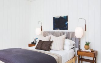 transitional bedroom wood bedside tables light wood bed frame with vertical striped headboard a couple of wall sconces black lampshade pendant