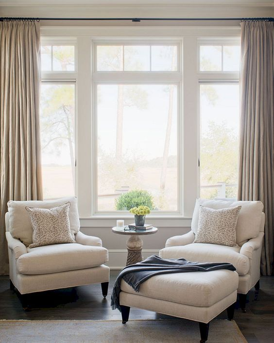 Coastal seating corner a couple of white armchair upholstered table in white large glass window light cream draperies