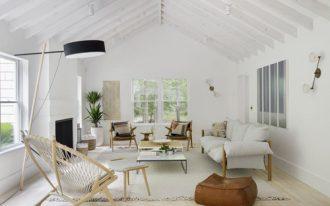 Scandinavian living room exposed wood beams in white white area rug light wood floors light wood furniture set dark brown beanbag floor lamp with black lampshade