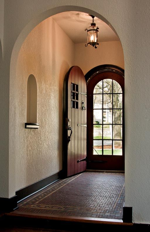 arched main entrance with stucco walls in white