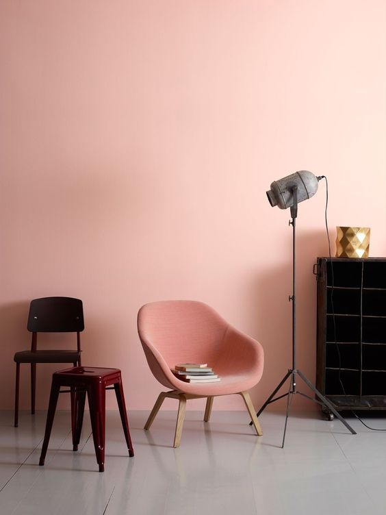 baby pink wall painted pink midcentury modern chair bold red side chair dark wood chair black finished wood rack tripod floor lamp