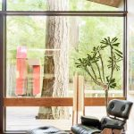 Clear Glass Wall Panel Slanted Wood Ceiling Midcentury Modern Chair And Table Colorful Shag Rug