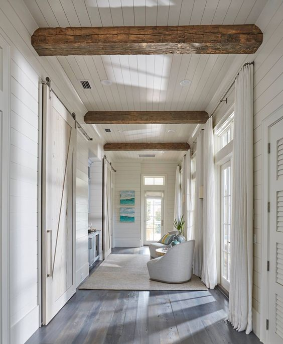 coastal hallway idea wood planked wall in white dark wood floors white draperies exposed wood beams white area rug barn door in light tone
