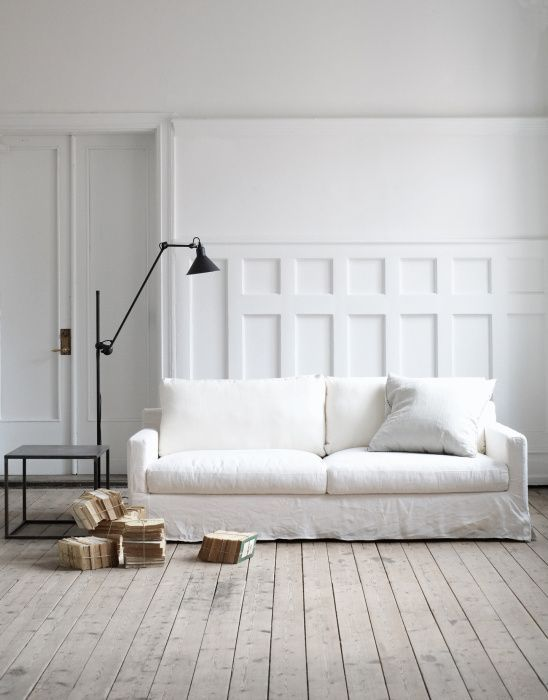 crisp white couch slipcover crisp white walls black finish metal side table black finish floor lamp in modern style whitewashed wood planked floors