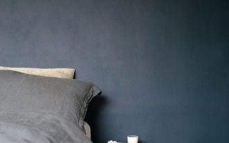 deep blue wall painting idea gray bedding treatment dark wood floors dark wood bedside table ornate wool basket in white