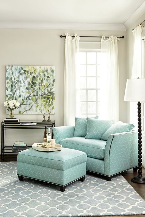 light blue loveseat with throw pillows light blue upholstered table black finish metal rack white sheer windows blue patterned area rug dark wood floors stand lamp with white lampshade