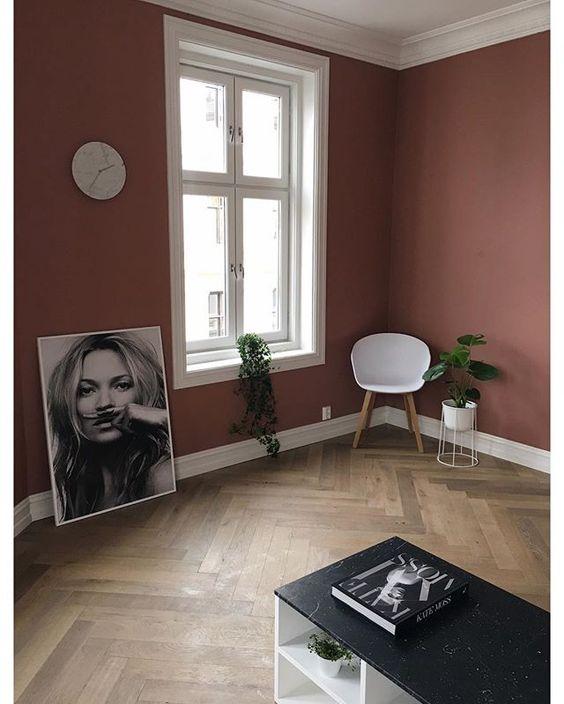 matte pink wall painted white window trims and ceilings herringbone patterned wood floors corner modern chair smaller greenery on pot