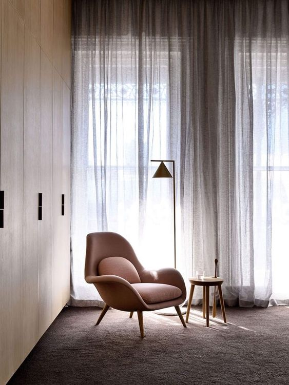 minimalist and semi transparent curtains in broken white midcentury modern lounge chair in baby pink round wood top side table