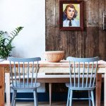 Modern Rustic Dining Room With Poppy Color Addition Poppy Blue Dining Chairs Light Wood Dining Table Reclaimed Wood Wall With Ornate Framed Painting