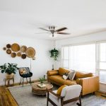 Modern Style Living Room In Neutral Tone Leather Couch In Earthy Brown White Chair Gray Area Rug Wood Floors Potted Greenery