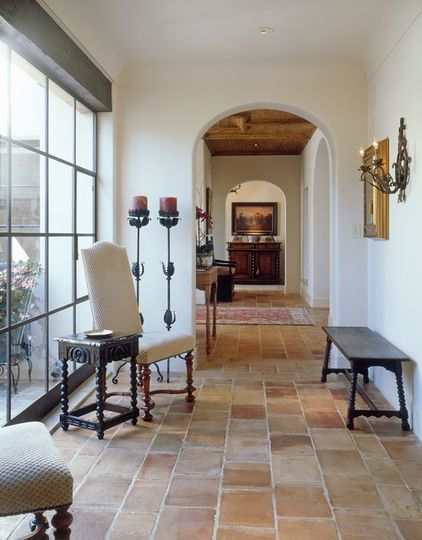 no trim Spanish colonial interior idea warm toned tile floors semi arched door white stucco walls modern glass door