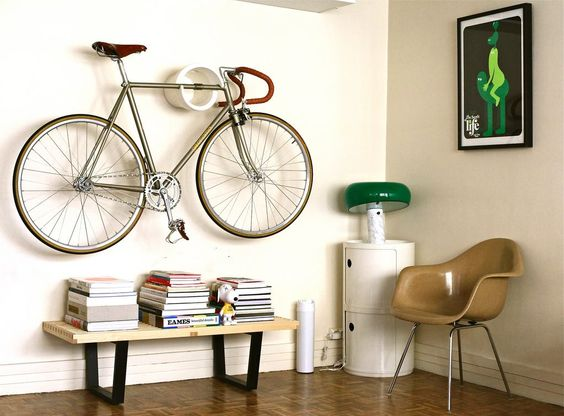 reading corner idea modern wood table with heavy metal legs midcentury modern chair in beige with tiny angled legs corner side table in white hanging bicycle