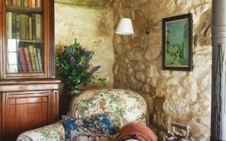 small seating area in rustic stoned wall idea chair slipcover with flower prints wood side table wood bookcase with clear glass door