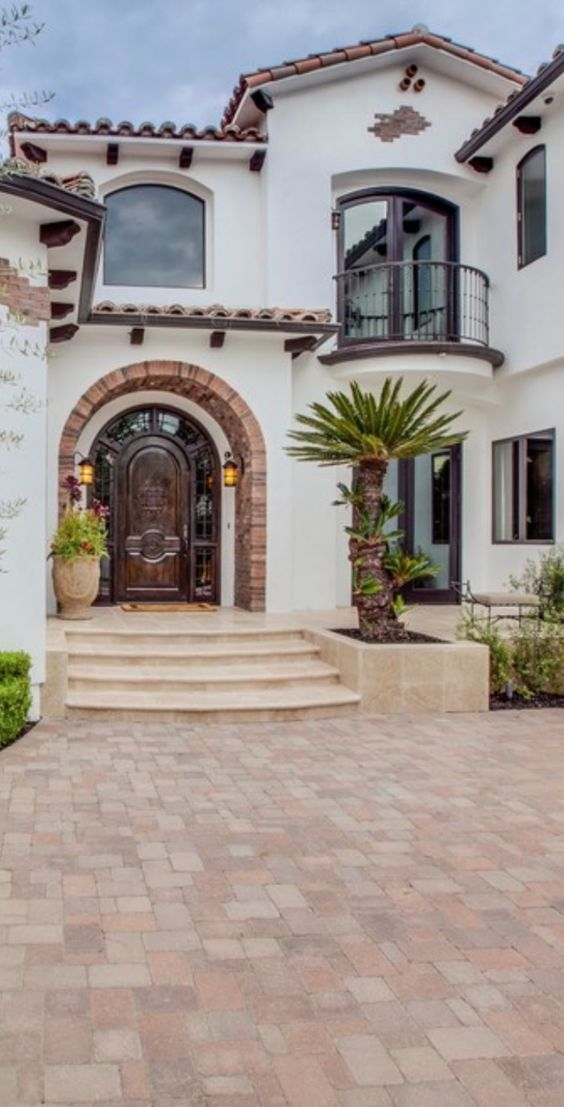 thick Spanish style house with white stuco exterior walls curved doors and windows arched roofs