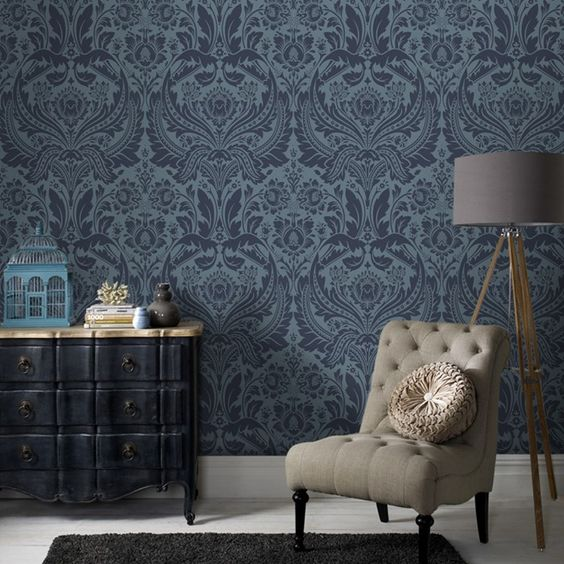 Damask print wallpaper in deep blue antique console table tufted chair with round throw pillow tripod floor lamp