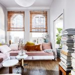 Danish Inspired Living Room Blush Tone Sofa With Throw Pillows A Couple Of White Round Top Coffee Tables Oak Floors Bamboo Window Shades Extralarge Pendant Lantern In White