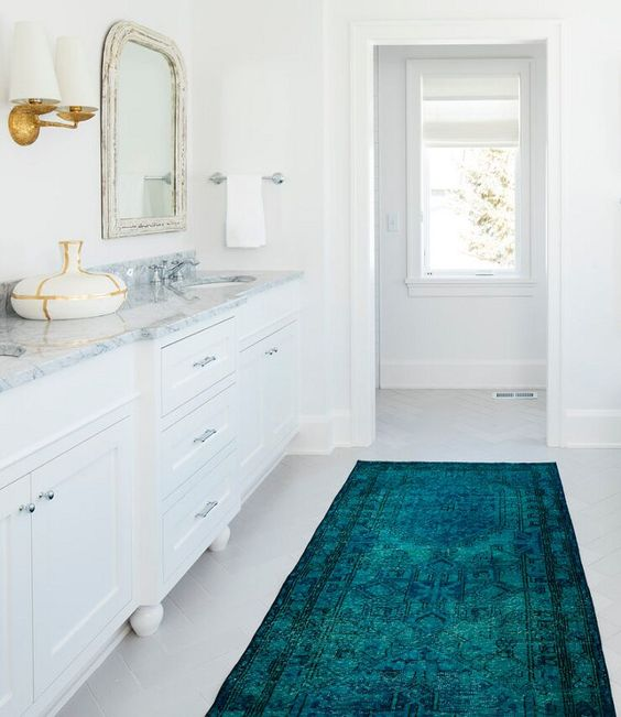 all white bathroom marble countertop with white cabinetry framed vanity mirror teal runner