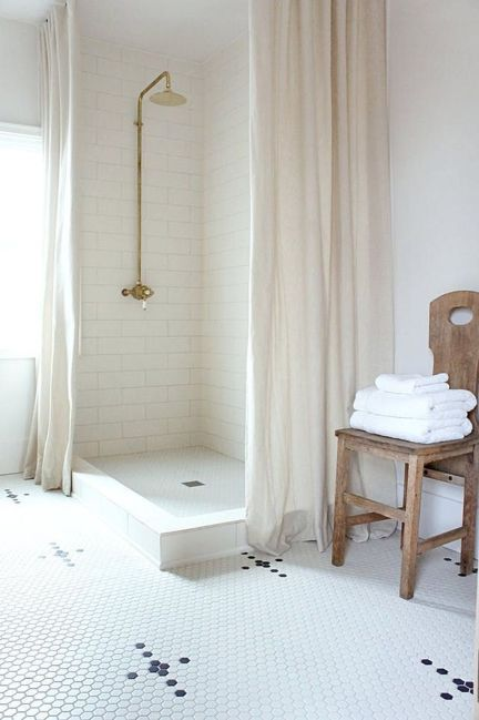all white walk in shower subway ceramic tile walls in white white mosaic tile floors floor to ceiling shower curtains in dusty white wood chair as the table