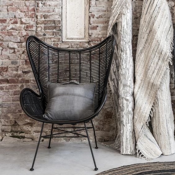 black rattan egg chair with black throw pillow whitewashed brick walls decorative fabric in shabby white