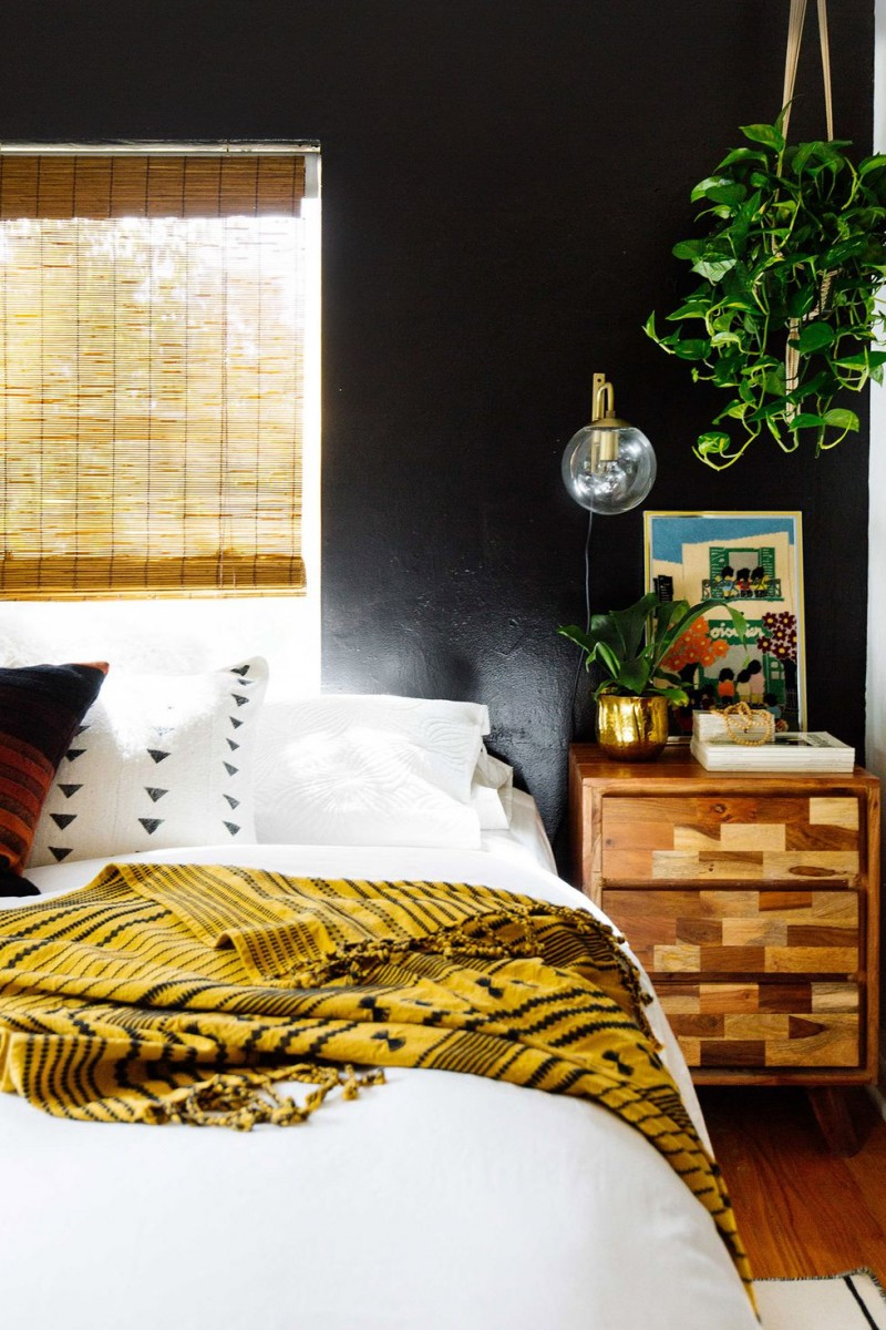 black wall painting wood nightstand white bedding bamboo shade glass window hanging greenery