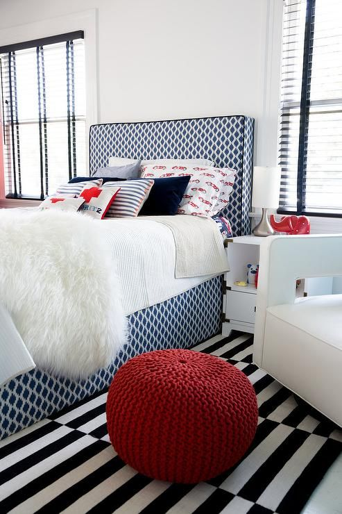 black white bed frame with headboard white bed linen shag throw blanket white black striped rug wool knitted pouf in bold red