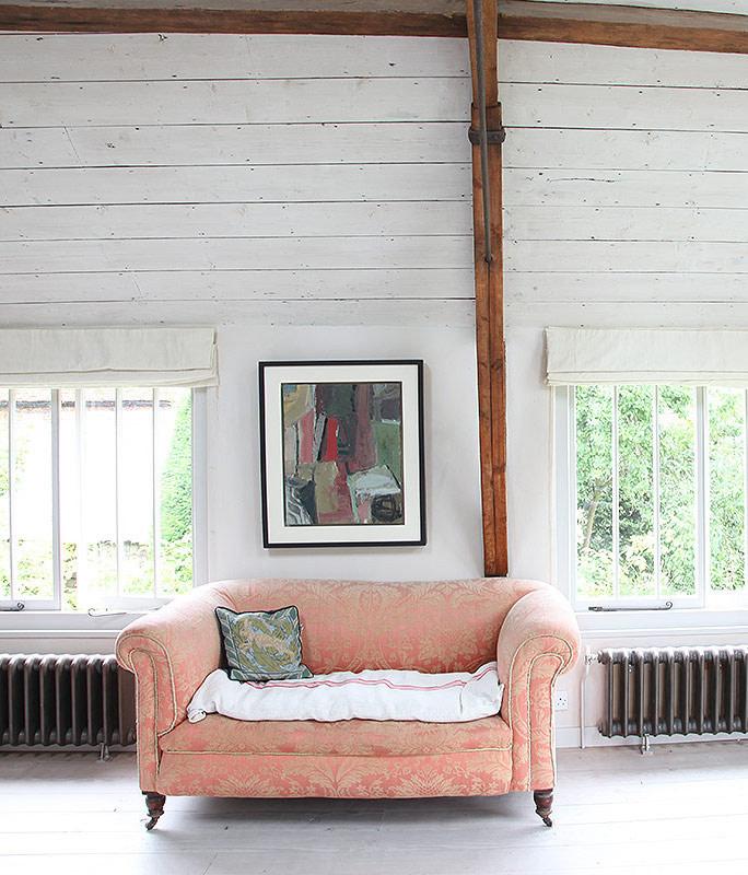 blushy pink vintage sofa with Damask patterns whitewashed wood plank wlals white wood floors