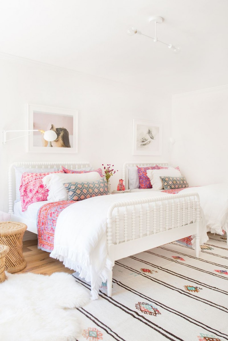 boho shared bedroom idea white bed frames with headboards bright pillows and sheets patterned rug white shag rug abstract photographies