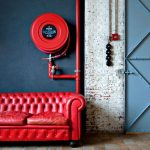 Bold & Stylish Industrial Living Room Red Tufted Leather Sofa In Classic Style Round Velvet Area Rug In Red Stucco Floors Shabby Brick Walls Red Pipes Blue Painted Metal Door