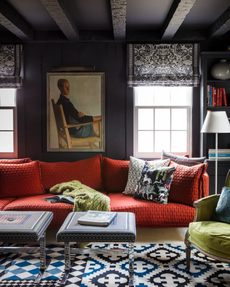 charcoal walls and ceilings exposed wood beams bold red sofa bold patterned area rug