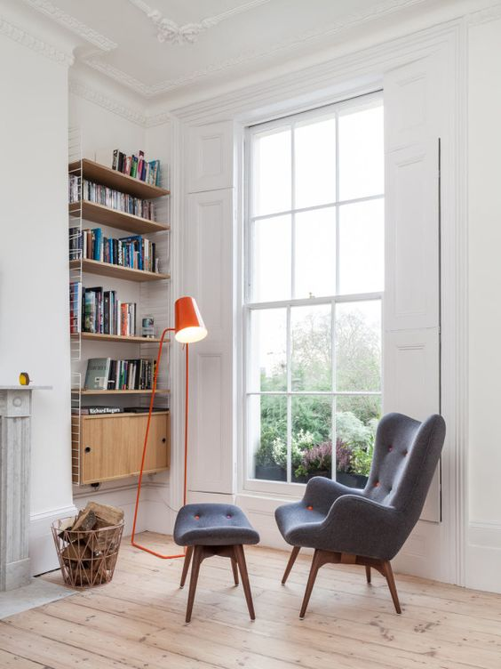 clean and contemporary reading nook armchair with ottoman bright orange floor lamp wired bookshelves light wood floors glass window with trims