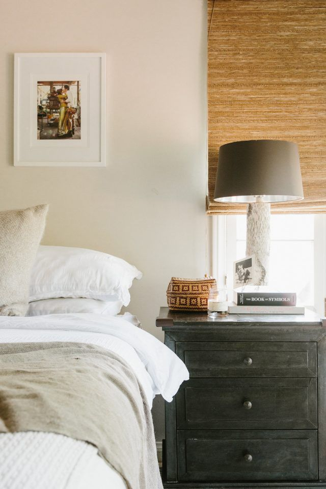 cozy and warm feel bedroom white bedding white wall painting window shade in earthy brown gray nightstand