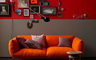 deep orange sofa in midcentury modern style round top wood stool half way gray and red walls plenty of wall decors dark area rug with round shape accents
